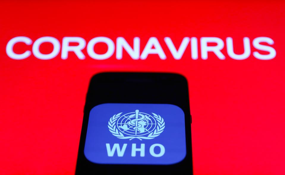 World Health Organization logo on smartphone screen against a red backdrop and the word coronavirus