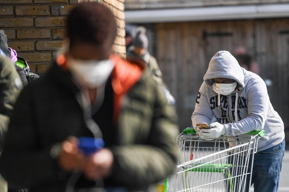 Shoppers Line Up Outside A Supermarket