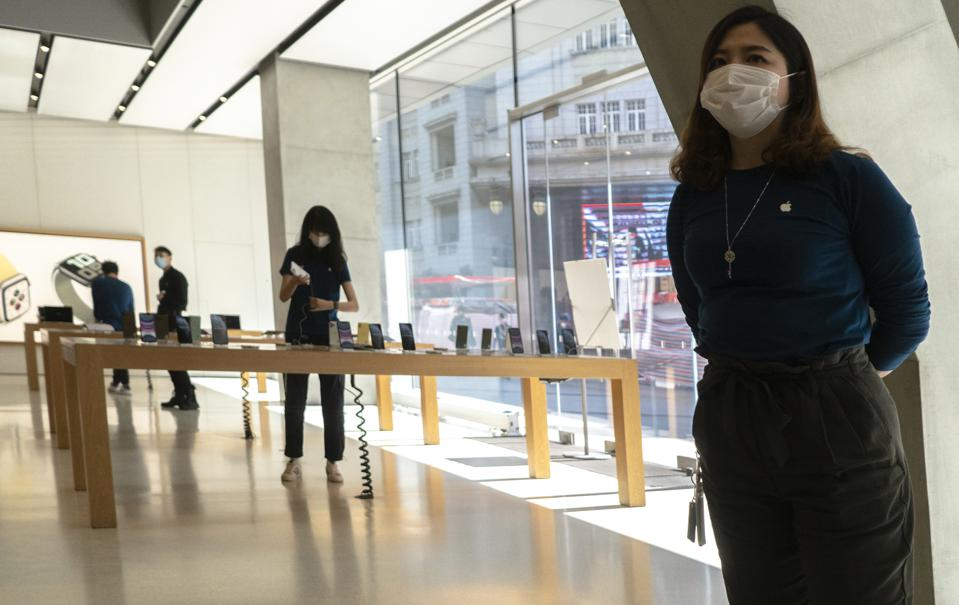 Customers and working staff are all wearing face masks in an Apple store.