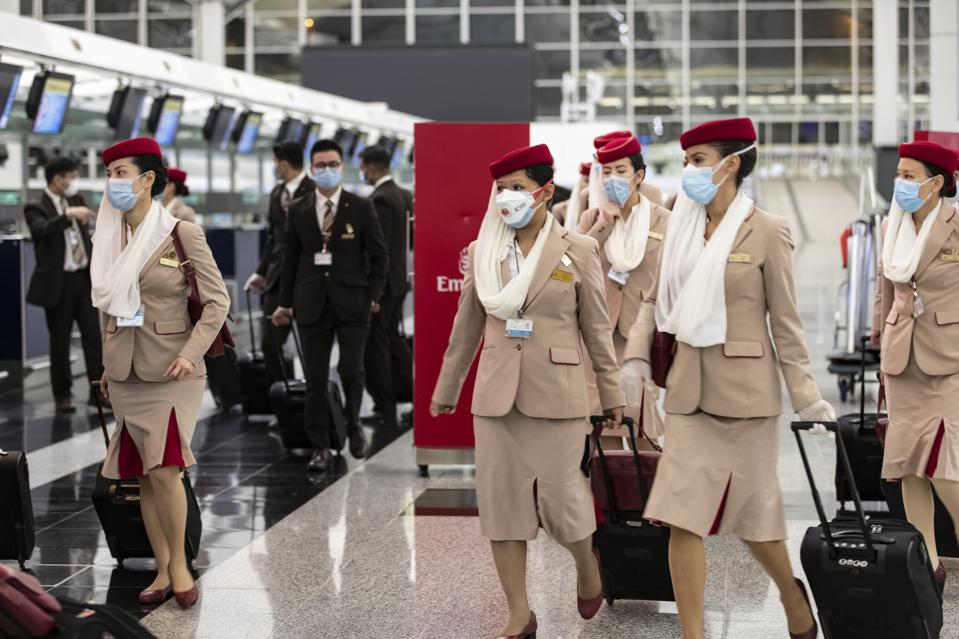 Crew members from Emirates airline leaving Hong Kong airport wearing masks.