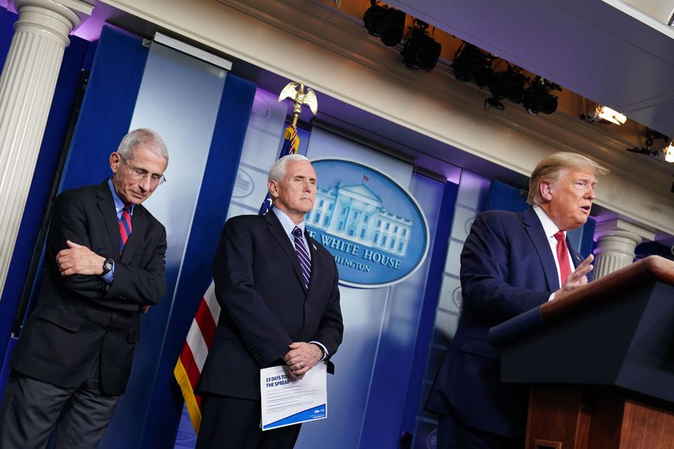 Fauci, Pence, and Trump speak at a press briefing.