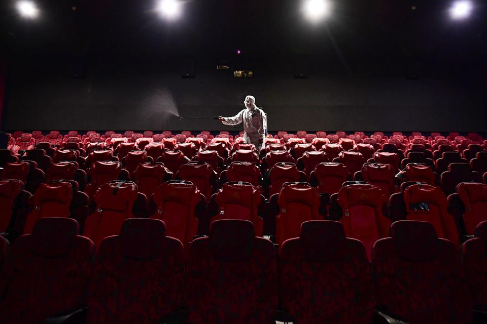staff member spraying disinfectant at a cinema preparing to reopen after closing due to the COVID-19 coronavirus, in Shenyang China.
