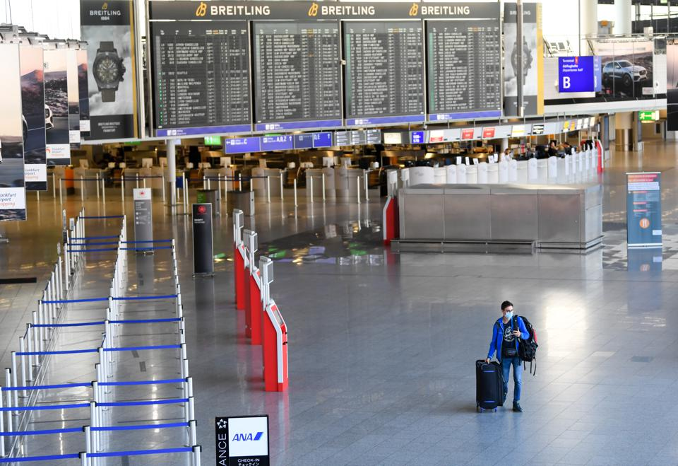 At Frankfurt Airport, a passenger walks through the empty departure.