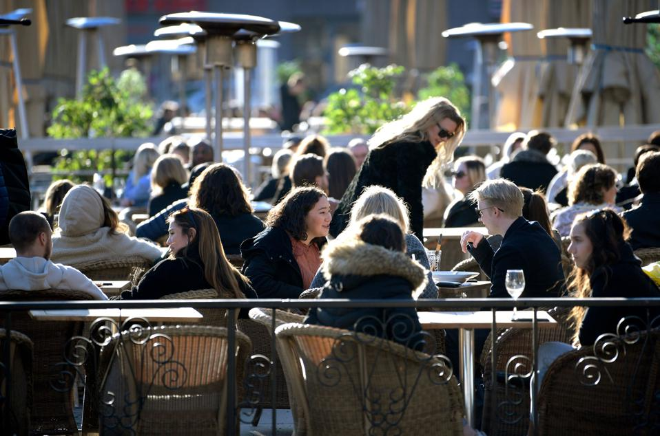 Stockholm locals enjoying a cold, sunny day in an open air restaurant.