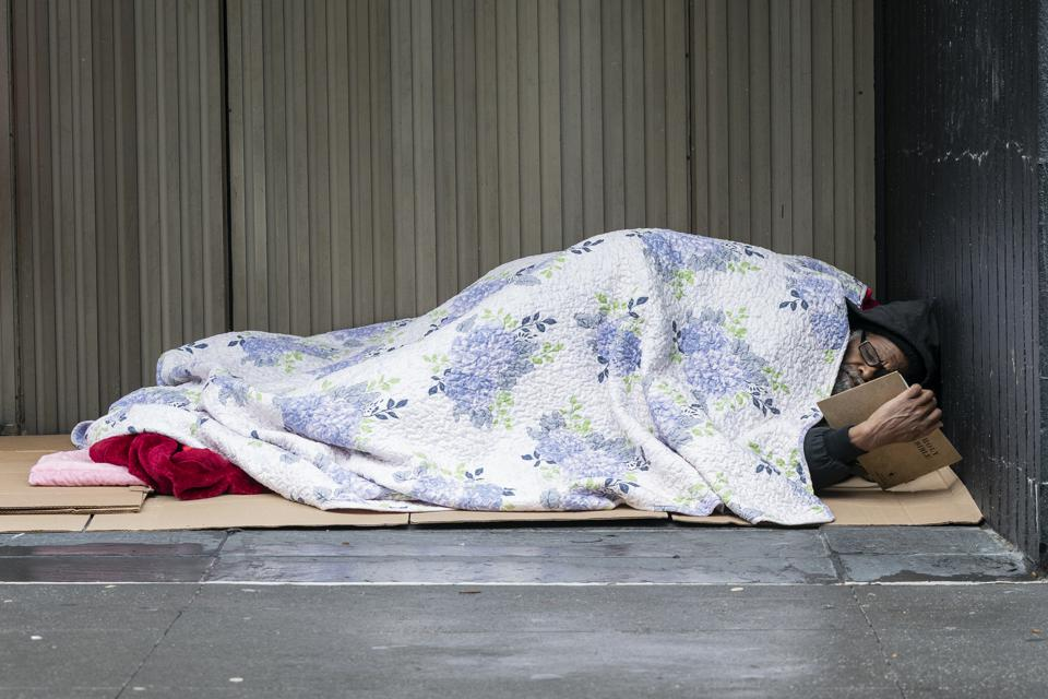 Homeless person lays under blanket on street and reads Holy...