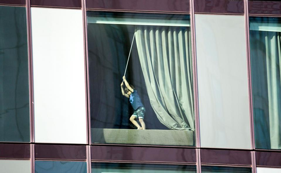 A boy pulls on a curtain during a hotel quarantine in Australia
