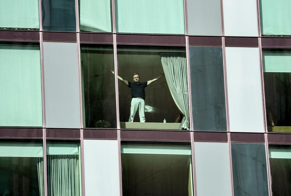 Man gestures from window of covid-19 quarantine hotel in Australia