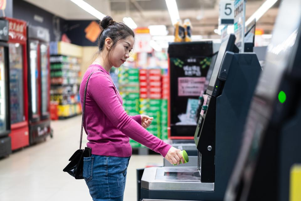 female checkout by automatic payment machine in supermarket