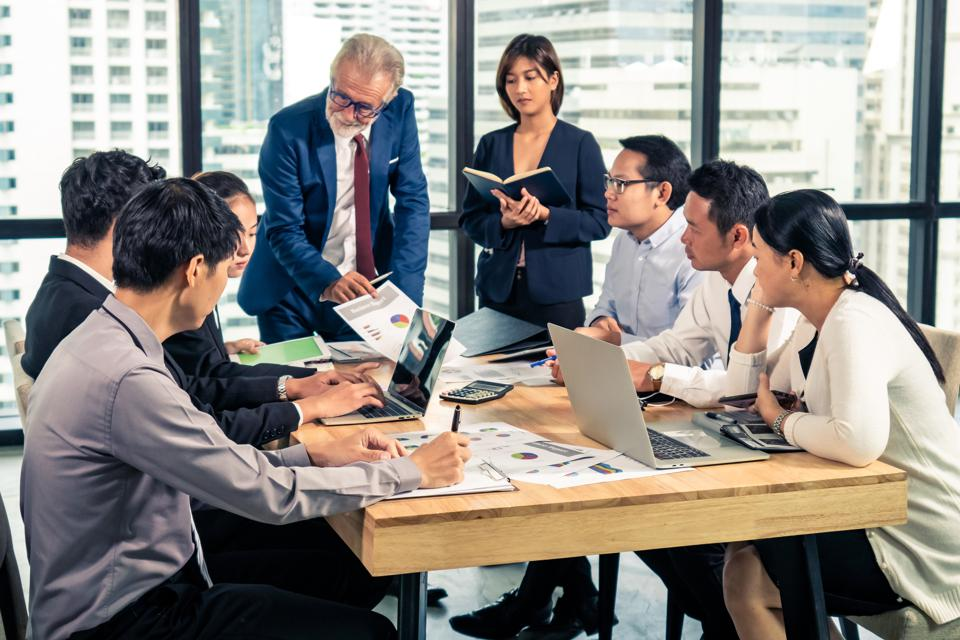 Group of Asian business people man and woman employee meeting with CEO or manager advisor briefing and discussing teamwork business plan in office conference room. Business team meeting seminar concept.