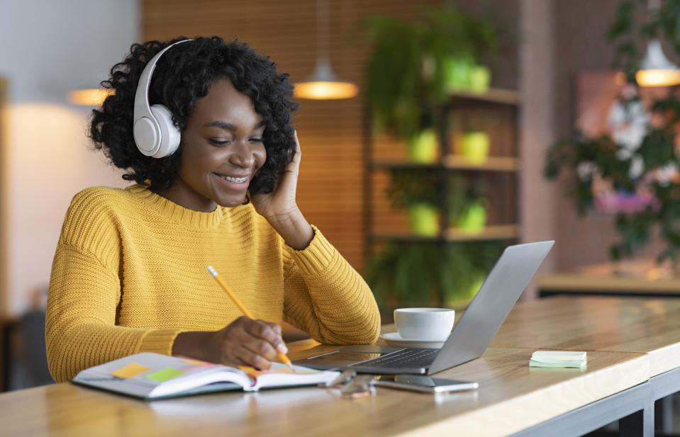 Black girl in headphones studying online, using laptop at cafe