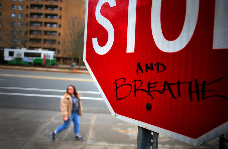 Graffiti on a stop sign in Brookline, Massachusetts, offers advice to stop and breathe.