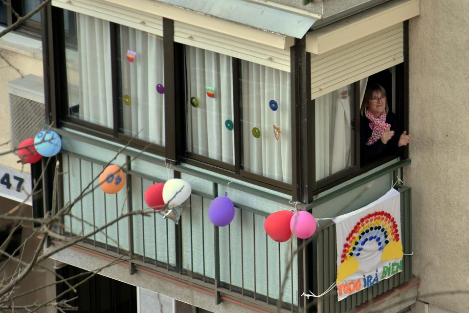 A woman applauds from the terrace of her house to show...