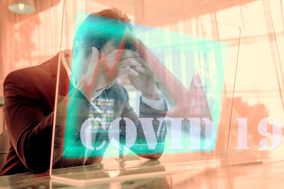 Concept of financial problems. Man holding his head while the markets plunge serious Covid-19 ,corona virus effect health investment .