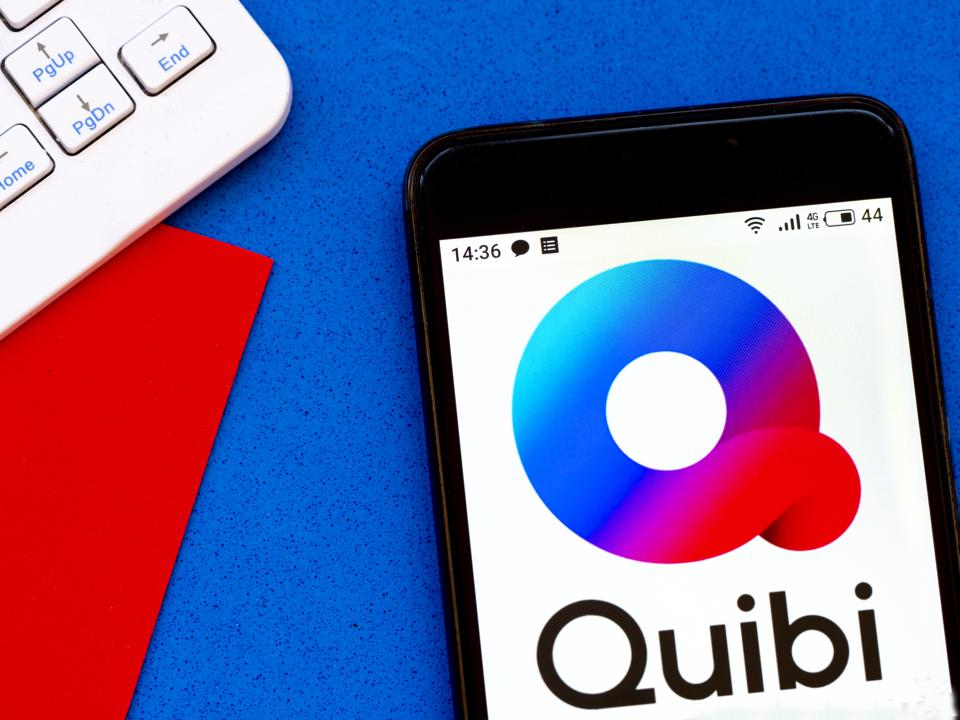 In this photo illustration a Quibi logo seen displayed on a...