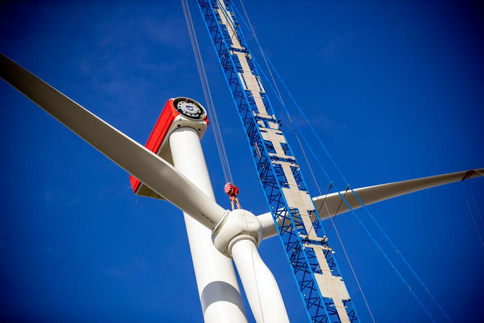 A crane lifts a propeller to be installed on a wind turbine against a blue sky.