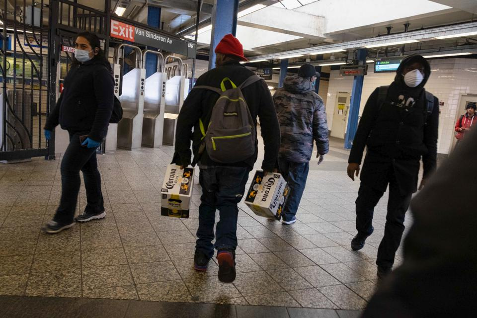A man is seen carrying two cases of Corona beer at the...