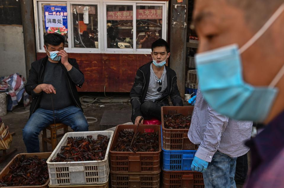 This photo taken on April 15, 2020 shows venders wearing face masks as the offer prawns for sale at the Wuhan Baishazhou Market in Wuhan in China's central Hubei province. - China's ″wet″ markets have gained a bad international reputation as the coronavirus roiling the world is believed to have been born in stalls selling live game in Wuhan late last year. (Photo by Hector RETAMAL / AFP) / TO GO WITH Health-virus-China,SCENE by Jing Xuan Teng (Photo by HECTOR RETAMAL/AFP via Getty Images)