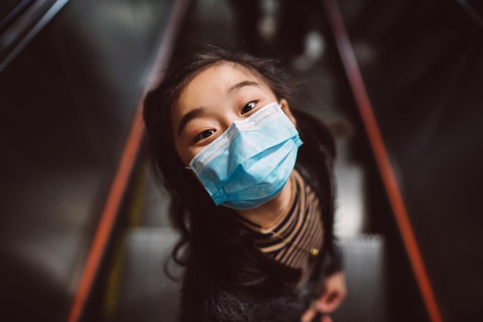 Little girl in medical face mask looking up at camera joyfully on escalator