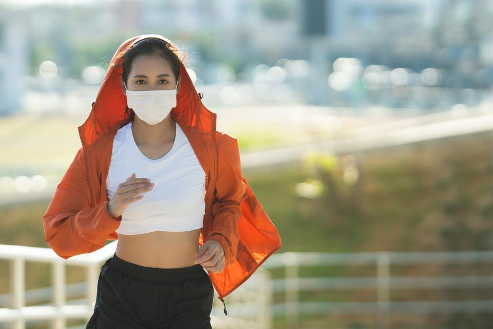Woman runners morning exercise she wears a nose mask. Protection against dust and viruses. COVID-19 coronavirus