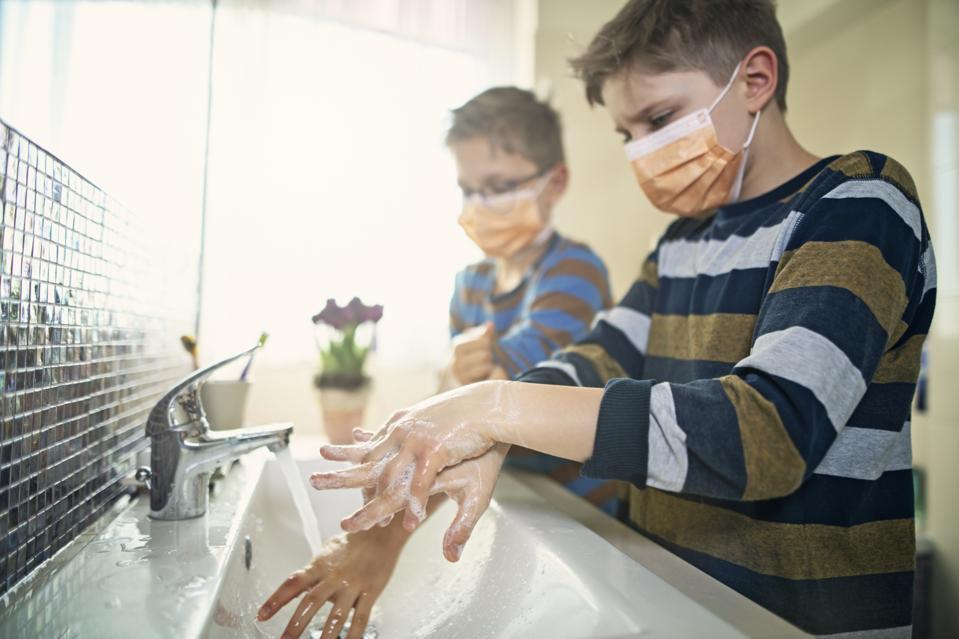 Little children wearing face masks amid the COVID-19 coronavirus pandemic, washing hands.