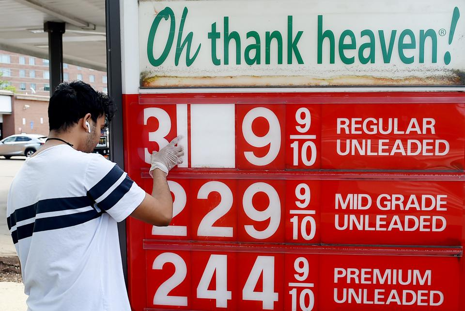An employee of a gas station adjusts gasoline pump prices as they plummeted last month.