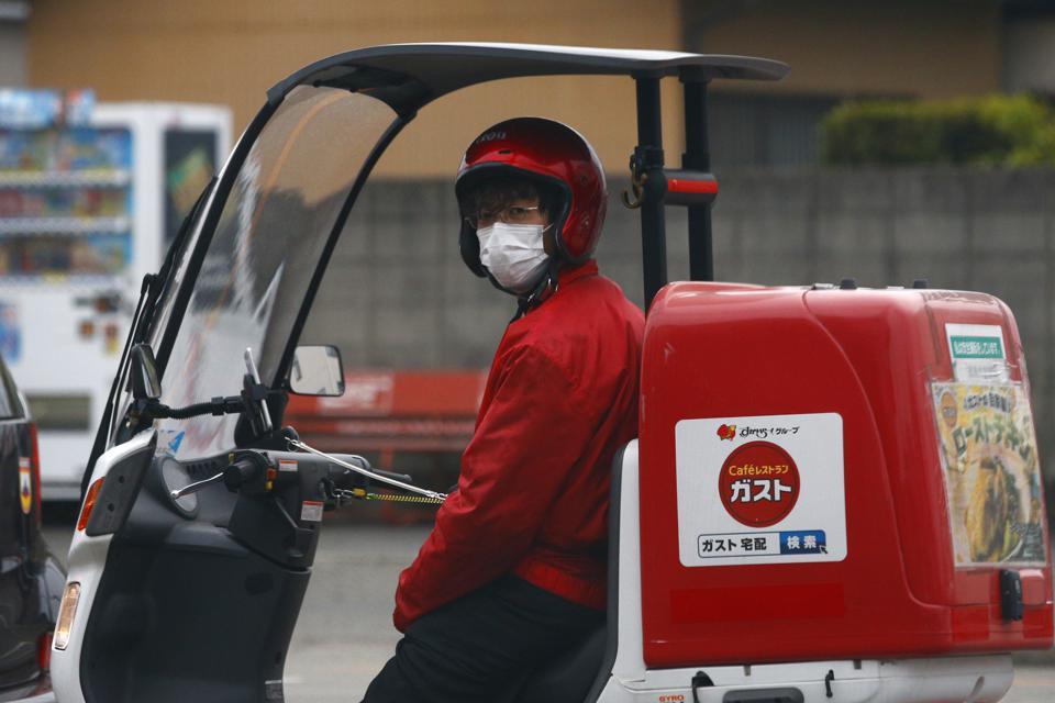 A food delivery man looks on while wearing a face mask as a...
