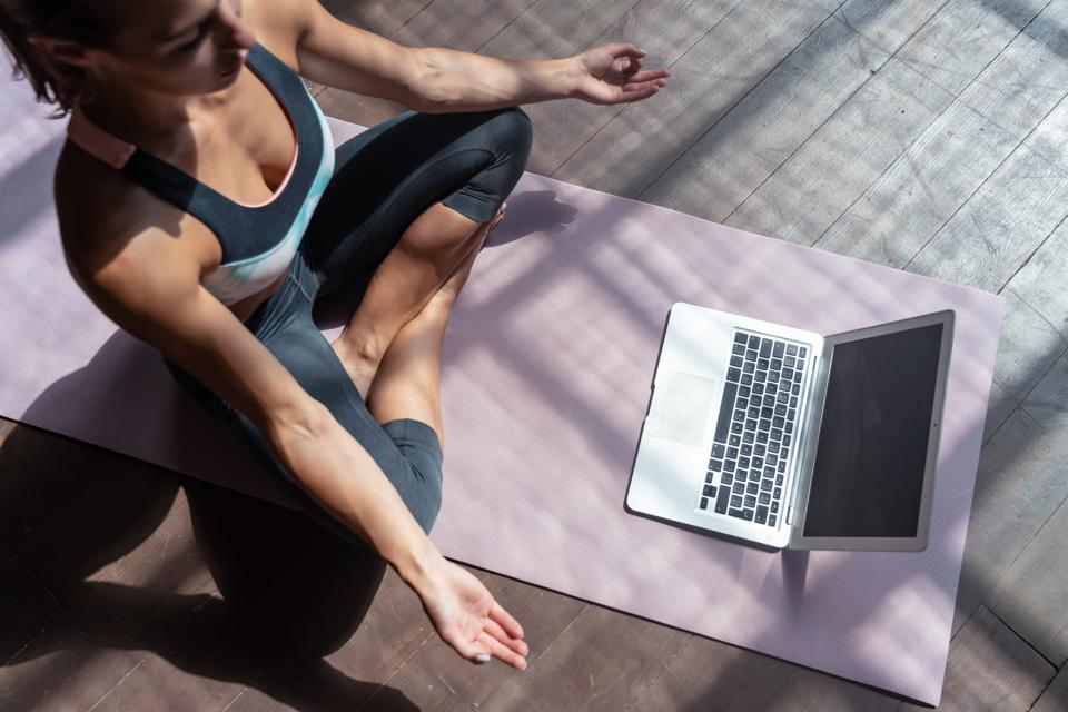 Woman sits on purple mat and practices yoga with a video