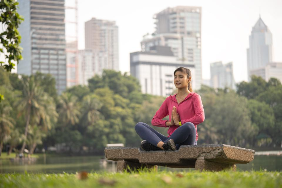 Woman meditating in a relaxing pose in city park.