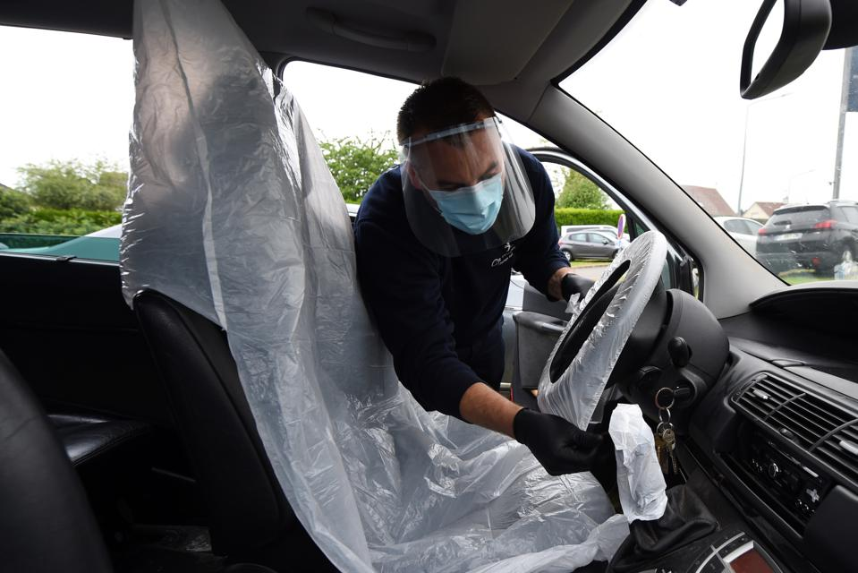 A dealership technician wearing a mask disinfects a car left for service.