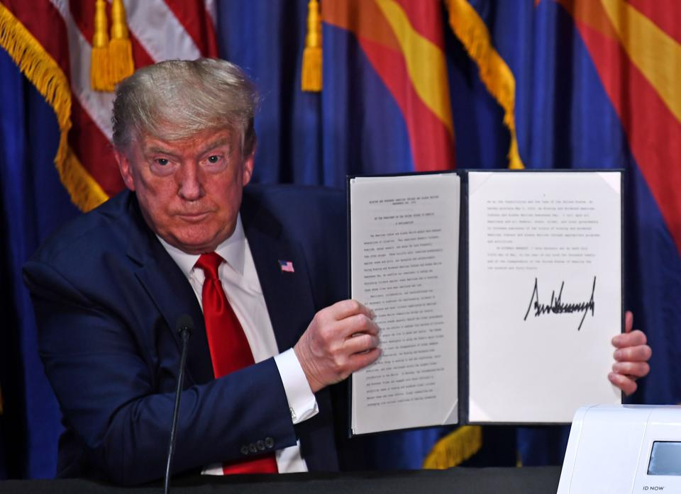 President Trump holds up a signed proclamation as he looks at audience earnestly.
