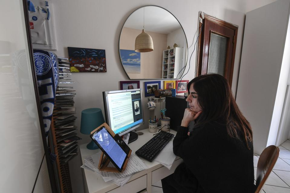 A woman works from her home in streaming contact with a...