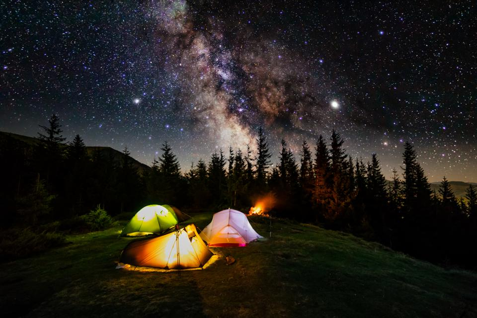 Tent camp in the mountains under a starry sky at night