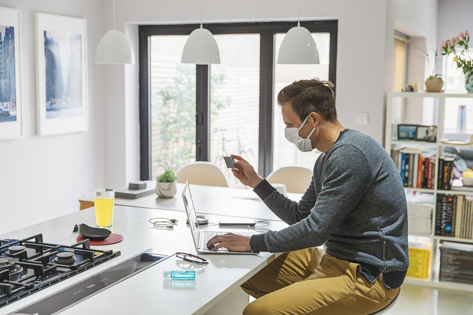 Man making online purchase whilst working from home