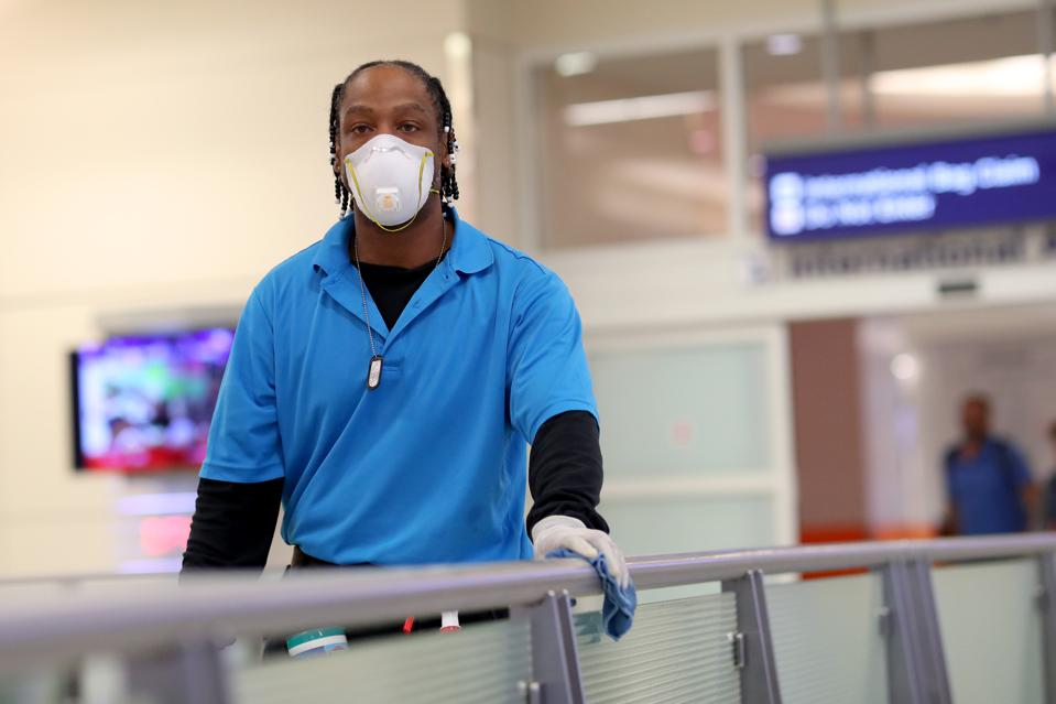 Hardy Williams disinfects areas of the international arrivals terminal at DFW airport on March 13, 2020 in Dallas, Texas.