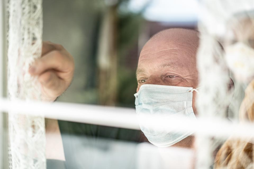 Senior man with mask looking trough window