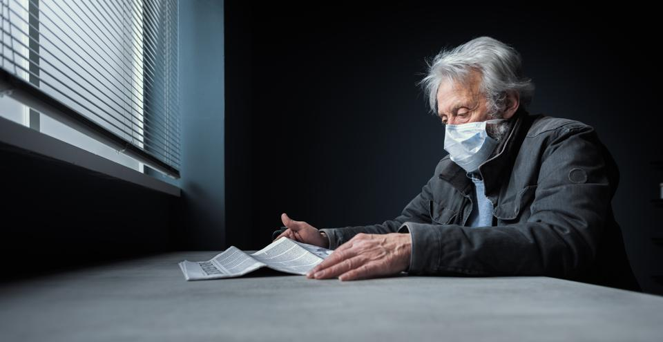 Quarantined senior sitting at home alone with surgical mask