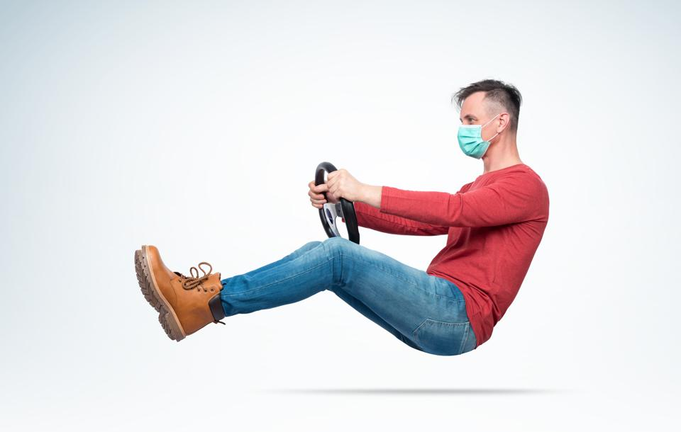 Man in respiratory mask drives a car while holding a steering wheel. Attention virus concept
