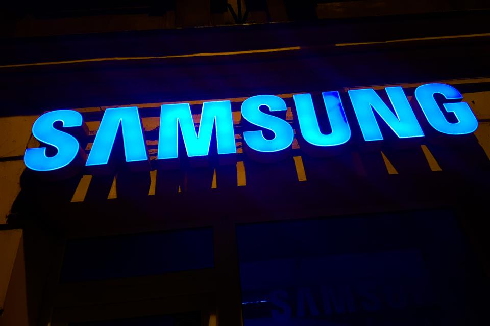 Samsung logo illuminated in glowing blue against a  black background
