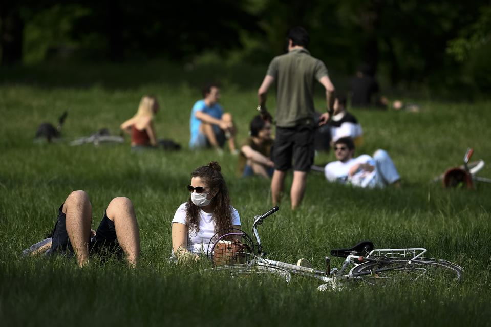 People are sitting on the lawn at crowded Parco del...