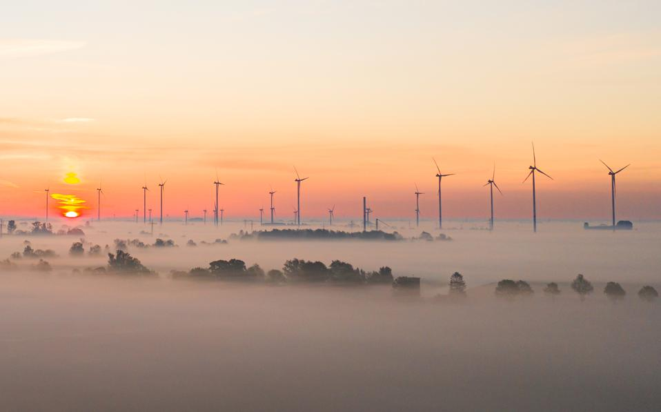 A wind farm covered with fog at sunrise, in Lower Saxony, Germany.