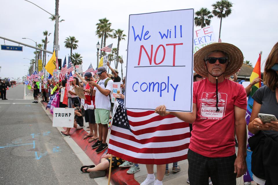 A protester holds a placard that says We will not comply...