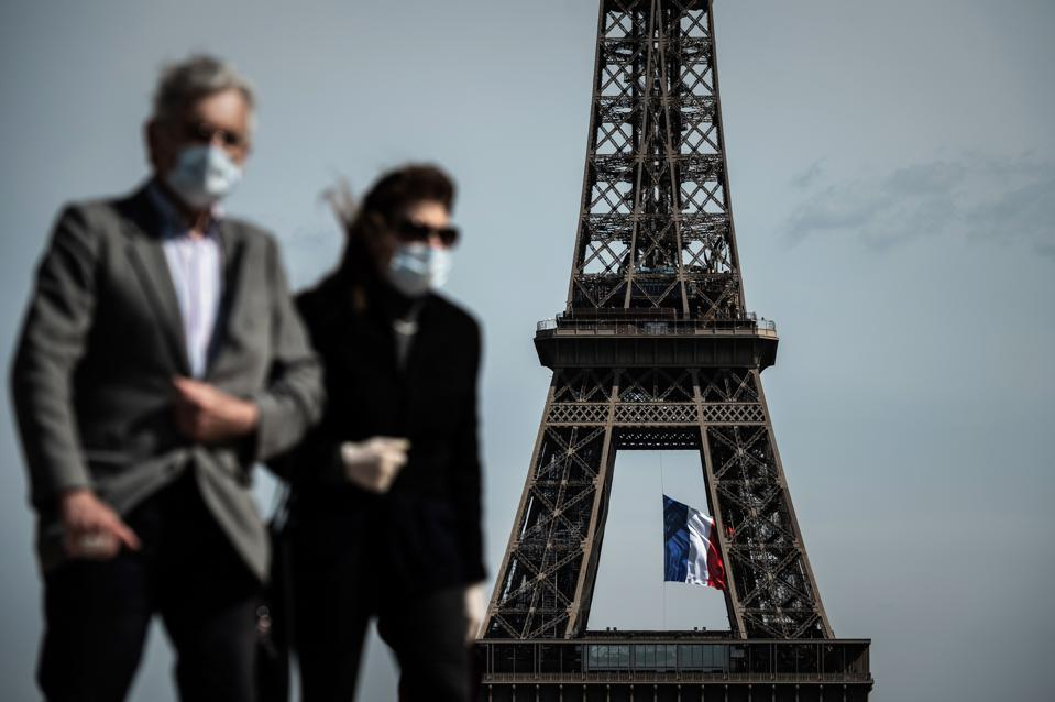 A man and a woman wearing face masks walk on Trocadero Plaza in Paris on May 11, 2020.