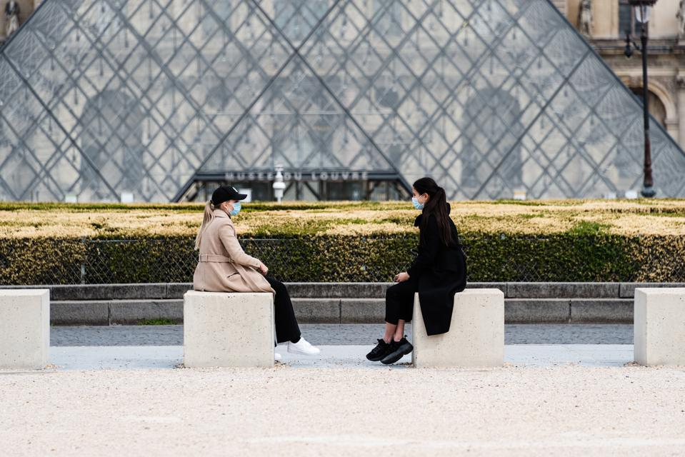 Two women wearing masks in front of the Louvre Pyramid on Tuesday, May 12, 2020 in Paris, the day after the end of the lockdown in France.