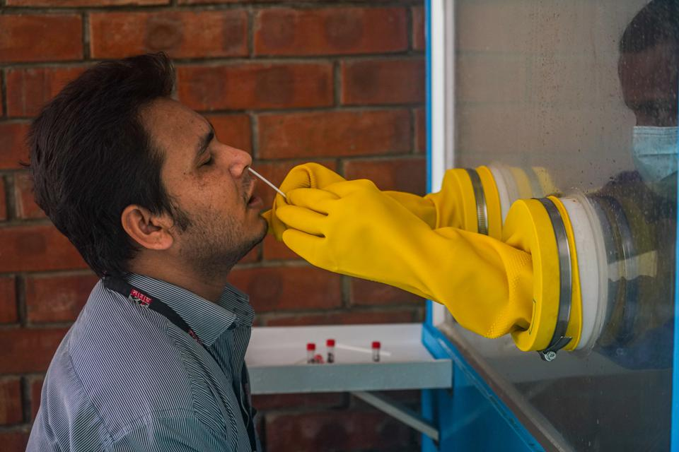 A man getting his sample collected by a health personnel...