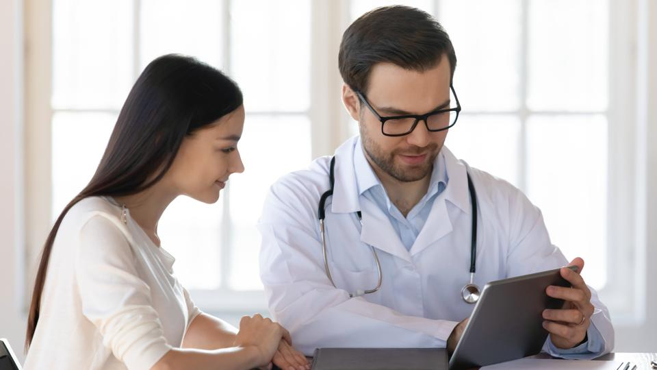 Pleasant doctor sharing treatment ideas with young woman.