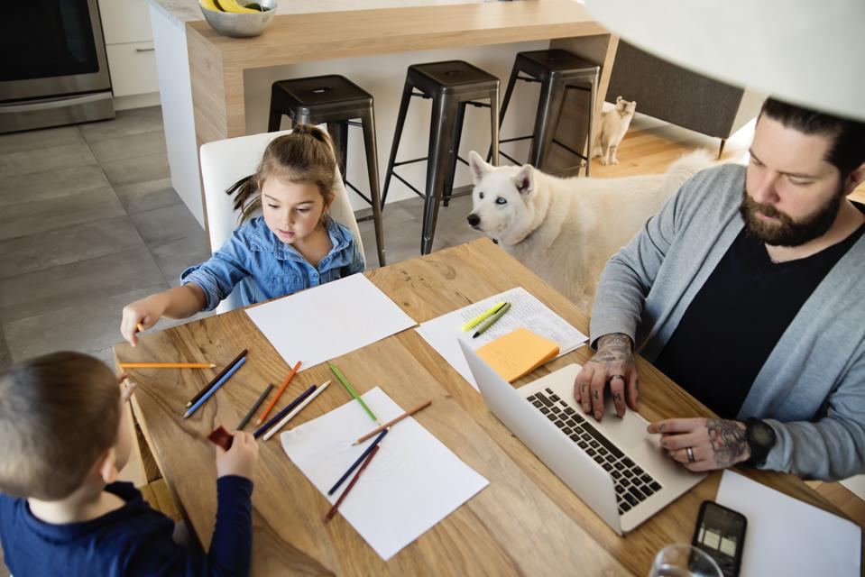 Father working from home with young children in quarantine isolation Covid-19