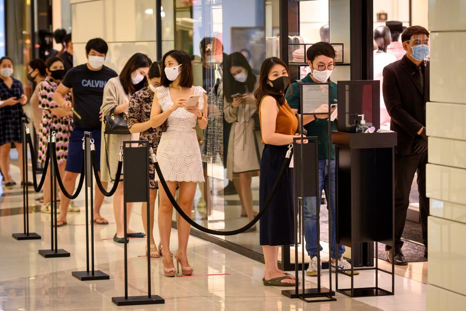 Shoppers standing in line to enter a luxury store at the newly reopened Siam Paragon mall, Bangkok.