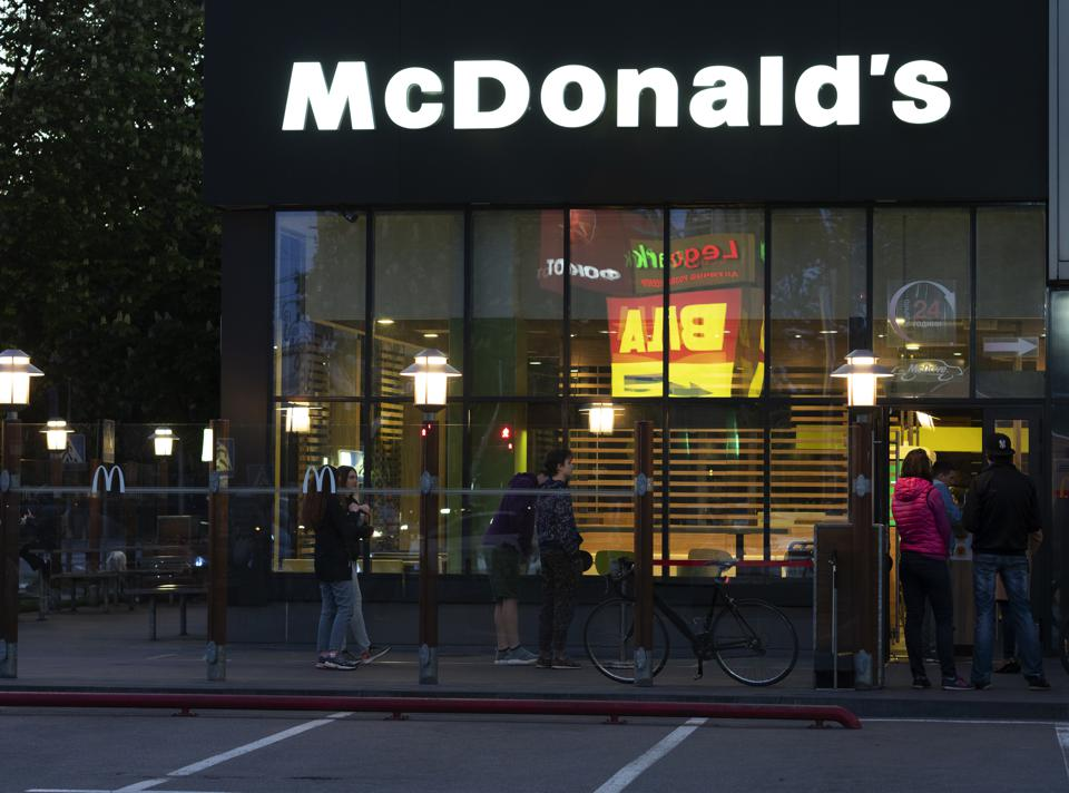 Visitors queue outside McDonald's restaurant in the evening...