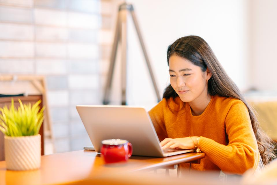 Young woman using laptop comfortably at home