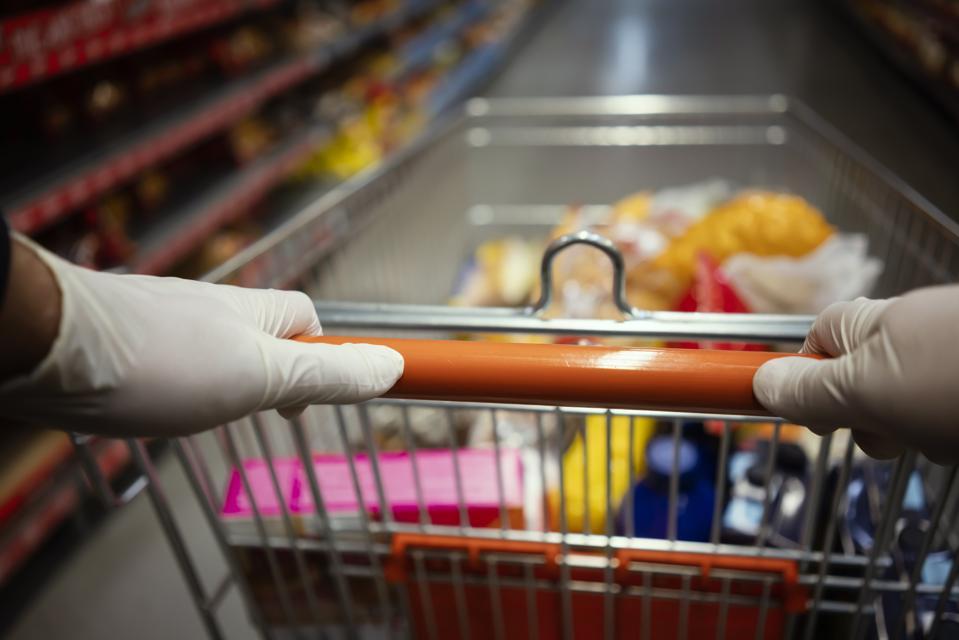 Woman using gloves during shopping in supermarket. Shopping during virus